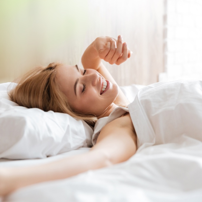 Frau beim Aufwachen im Bett.
