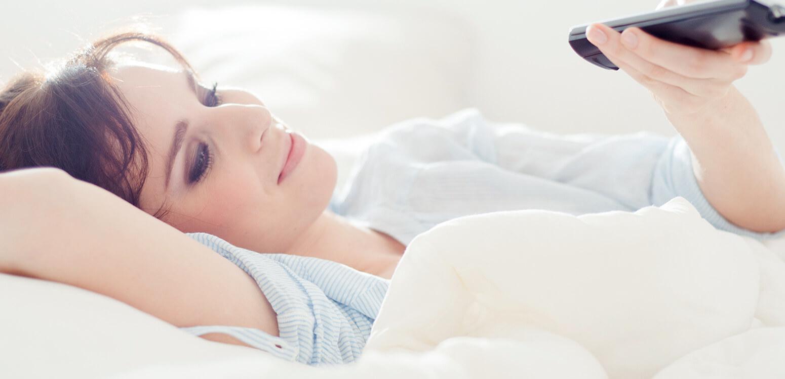 Frau guckt Fernsehen im Bett.